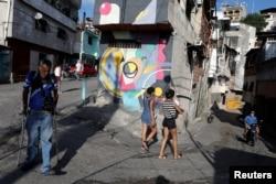 People walk pass a mural painted by Fabian Solymar in Petare slum, in Caracas, Venezuela, Aug. 7, 2019.