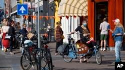 荷兰阿姆斯特丹,人们在排队购买传统的国王节糕点时,一些人戴着口罩,观察社会距离,以防止冠状病毒的传播。(2020年4月27日)