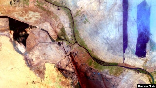 Smoke drifts south in this image of Al Basrah, located in southeastern Iraq, captured by the Landsat mission on April 4, 2003. The green circles from the center to the left of the image represent irrigated crops. (Courtesy USGS)