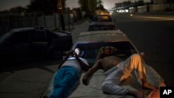 Andres Quintero, left, and Fermin Perez rest on top of Perez's car as they wait in line for over 20 hours to fill their tanks with gas in Cabimas, Venezuela, May 16, 2019.