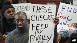 Desempleados muestran carteles durante una vigilia en Filadelfia.