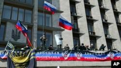 """Activistas ondean banderas rusas y muestran un cartel llamando a la formación de la """"República Donetsk""""."""