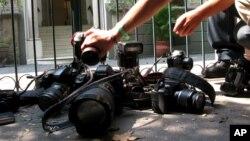 지난 4월 멕시코시티에서 열린 시위에서 사진기자들이 살해된 것으로 추정되는 레히나 마르티네즈 기자의 죽음에 항의하며 사진기를 땅에 내려놓고 있다. (자료사진)