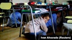 Các em học sinh chui xuống gầm bàn tại một trường học trong một cuộc diễn tập động đất ở Santiago, Chile, 13/11/2014.