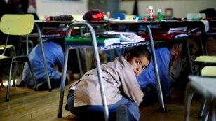 Şili'nin Santiago kentinde yapılan deprem tatbikatında masanın altına saklanan bir çocuk