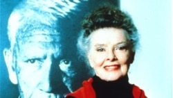 Katharine Hepburn poses in front of a picture of her longtime friend and co-star Spencer Tracy