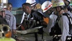 Los bomberos retiran de los escombros a una de las víctimas del colapso de un estacionamiento en el Miami-Dade College.