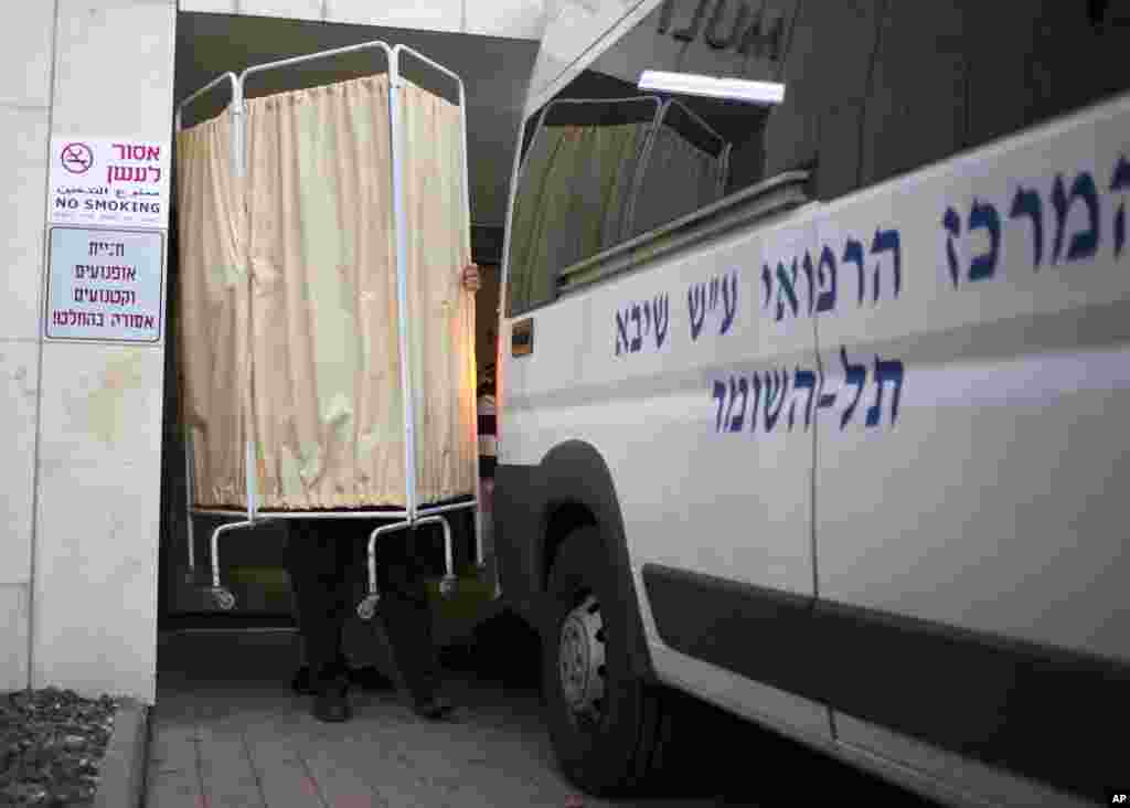 An Israeli policeman holds up a hospital curtain to block the view of the body of the late Prime Minister Ariel Sharon as it is transferred into an ambulance to be taken from the Sheba Medical Center near Tel Aviv, Israel, Jan. 11, 2014.