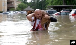 FILE - Louis Marquez carries his dog Dallas through floodwaters after rescuing the dog from his flooded apartment in Houston.