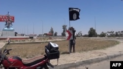 FILE - An image taken from video uploaded Aamaq News Agency, a YouTube channel which posts videos from areas under the Islamic State group's control, allegedly shows an IS fighter hanging a flag of the group in a street of Ramadi, Iraq.
