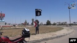 Chiến binh Nhà nước Hồi giáo cắm cờ đen trên đường phố Ramadi.