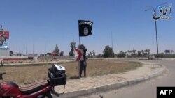 Seorang militan ISIS memasang bendera di sebuah jalanan di kota Ramadi (foto: dok).