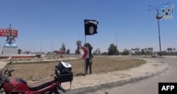 An image taken from a video uploaded on May 18, 2015 by Aamaq News Agency, a Youtube channel which posts videos from areas under the Islamic State (IS) group's control, allegedly shows an IS fighter hanging a flag of the group in a street of Ramadi, the I