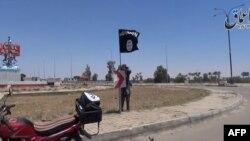 Youtube一段视频截图显示,一名伊斯兰国武装分子据称在拉马迪的街道上挂起伊斯兰国的旗子 (2015年5月18日)
