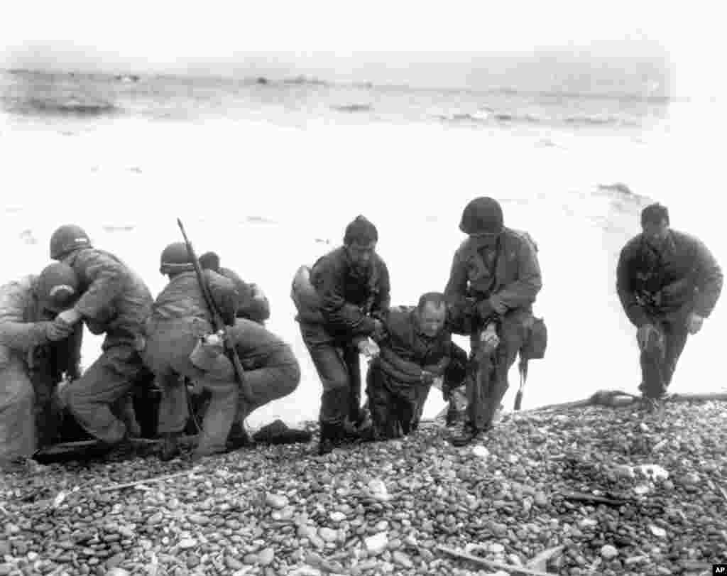 Members of an American unit reach Utah Beach on a life raft after their landing craft was hit and sunk by German coastal defenses. Here soldiers help their exhausted comrades ashore during the Normandy invasion, June 6, 1944.