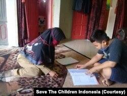 Seorang anak yang sedang belajar di rumah dengan didampingi seorang guru kunjung di desa Malei, Kecamatan Balaesang Tanjung. (Foto: Save The Children Indonesia)