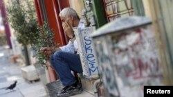 Một người đàn ông ngồi trên bậc thềm trước cửa hàng của mình ở trung tâm Athens, Hy Lạp sau vụ khoảng.
