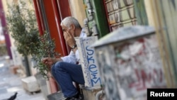希臘雅典一名商店主人坐在店前,對國家經濟感到失望。