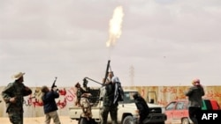 Libyan rebel fighters fire an anti-aircraft weapon at an airforce jet loyal to Qadhafi. (file)