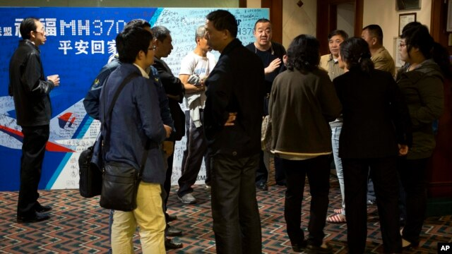 Relatives of Chinese passengers aboard the missing Malaysia Airlines flight MH370 chat outside the conference room during a briefing held by Malaysia officials at a hotel in Beijing, China, April 11, 2014.