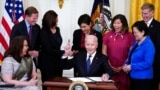 President Joe Biden smiles after signing the COVID-19 Hate Crimes Act, in the White House, May 20, 202. From left, Sen. Tammy Duckworth, R-Ill., Sen. Richard Blumenthal, D-Conn., Vice President Kamala Harris, Rep. Judy Chu, D-Calif., Rep. Grace Meng, D-NY, Rep. Don Beyer, D-Va.