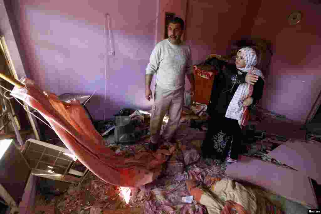 People examine damage inflicted on their house by a car bomb attack in al-Mashtal, Baghdad, March 19, 2013.
