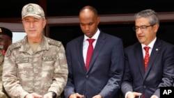 Le chef d'état-major turc, le général Hulusi Akar, à gauche, le Premier ministre somalien Hassan Ali Khayre, au centre, et l'ambassadeur turc en Somalie, Olgan Bekar, coupent le ruban inaugural du centre de formation militaire à Mogadiscio, Somalie, 30 se
