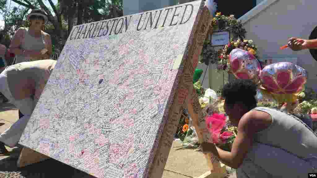 Des signatures sont apperçues sur un tableau de'Charleston United' à l'extérieur de l'église Emmanuel à Charleston, Caroline du Sud, le 21 juin 2015. (Amanda Scott/VOA)
