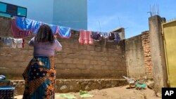 FILE - Reby hangs laundry outside her home in Beni, eastern Congo, May 1, 2021. Reby has accused a member of the World Health Organization of sexual exploitation.