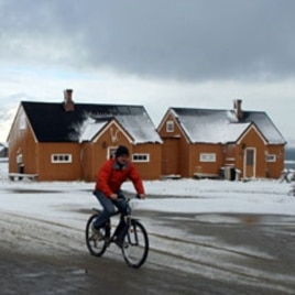 A man cycles through the Norwegian Arctic settlement of Ny Alesund as the first snows of winter arrive (File)