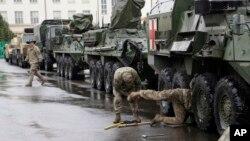Binh lính Quân đội Hoa Kỳ bảo trì xe bọc thép trong một chặng dừng chân ở Prague, Cộng hòa Séc, ngày 31 tháng 3 năm 2015.