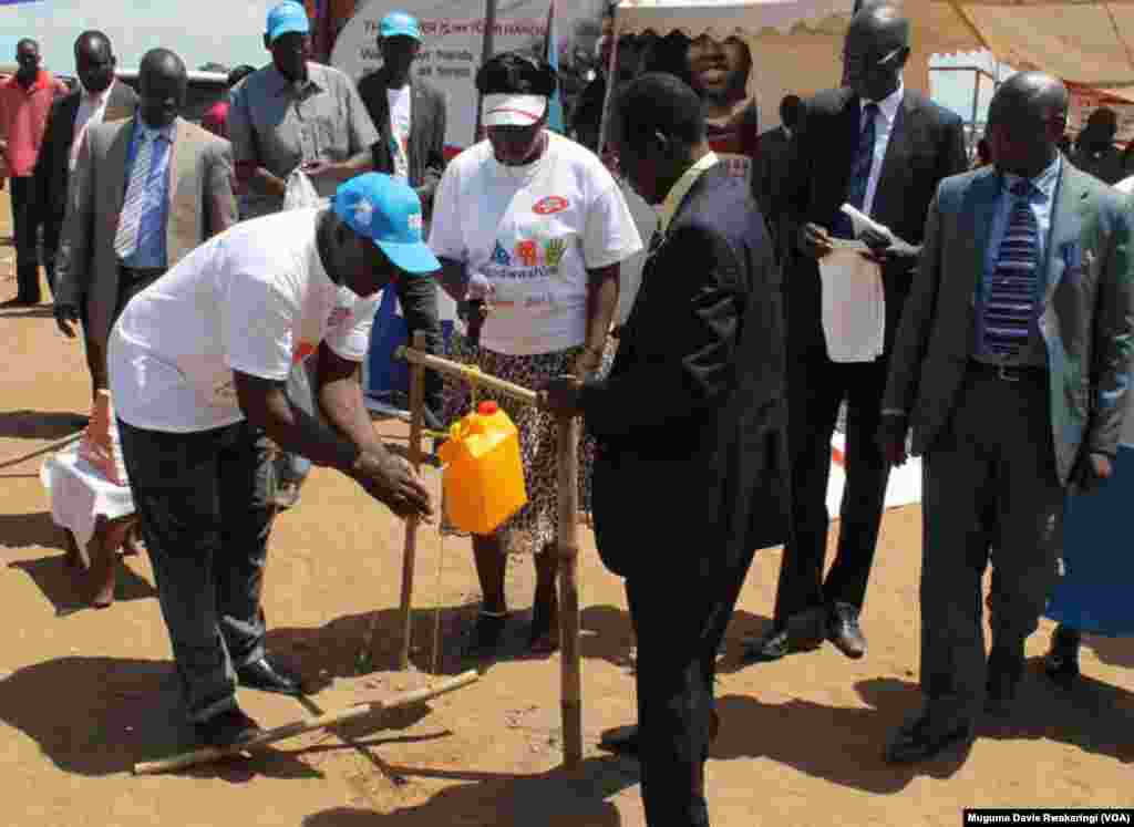 South Sudanese Vice President Wani Igga (centre, in suit) watches as a volunteer demonstrates how to wash hands with water from a jerry can.