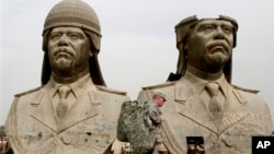 FILE - U.S. soldiers walk past two gigantic status of former Iraqi President Saddam Hussein in Baghdad, March 20, 2009.