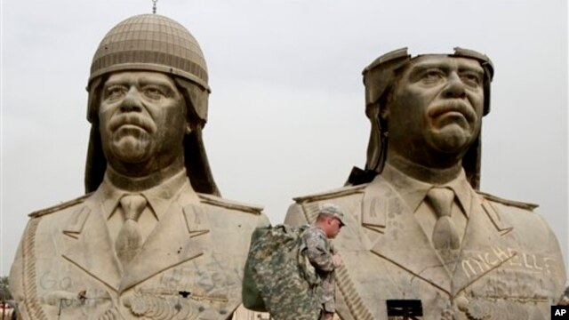 U.S. soldiers walk past two gigantic status of former Iraqi President Saddam Hussein in Baghdad, March 20, 2009.