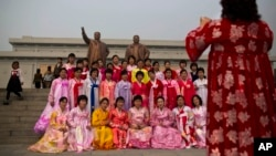 North Korean women in traditional dresses pose for a souvenir photograph in front of bronze statues of the late leaders Kim Il Sung and Kim Jong Il at Munsu Hill in Pyongyang on Tuesday, April 15, 2014.