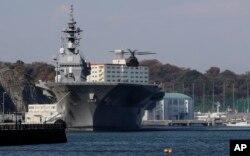 """在日本横须贺,一架直升机准备降落在日本海上自卫队""""出云""""号直升机驱逐舰的飞行甲板上。(2016年12月6日)"""