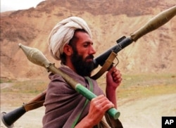FILE - A Taliban fighter walks with a Russian made RPG7 on the front line area in Gorband valley, 150 km northwest of Kabul, Afghanistan, May 3, 1997.