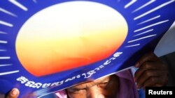 A woman holds a poster bearing the logo of the Cambodian National Rescue Party (CNRP) during a protest demanding a free and fair general election, May 20, 2013.