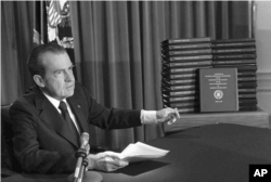 FILE - President Richard M. Nixon points to transcripts of White House tapes, April 29, 1974.