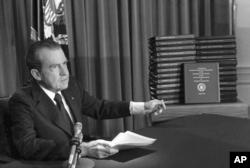 FILE - President Richard M. Nixon points to transcripts of White House tapes, April 29, 1974.