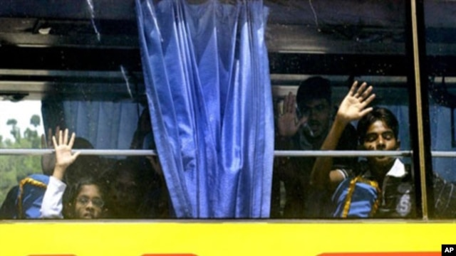 Sri Lankan children wave as they and other ethnic Tamil migrants leave the Merak seaport in Banten province by bus bound for a detention facility as they finally agreed to be relocated, 19  Apr 2010