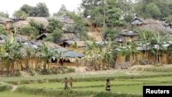 Children stand near camps housing Rohingya refugees on hills in Kutupalong, Bangladesh, May 31, 2015.