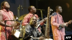 FILE - Toumani Diabaté, center, of Mali plays on his kora, an African harp, in Budapest, Aug. 11, 2006.