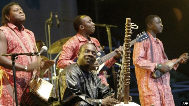 FILE - Toumani Diabaté, center, of Mali plays on his kora, an African harp, in Budapest, Aug. 11, 2006.