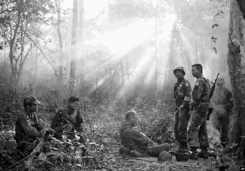 Tháng 01-1965: Ánh mặt trời xuyên qua khu rừng Bình Giả, Việt Nam trong lúc binh sĩ Việt Nam Cộng Hòa và cố vấn Mỹ tạm nghỉ sau một đêm căng thẳng chờ Việt Cộng phục kích, nhưng điều đó chẳng xảy ra. (AP)