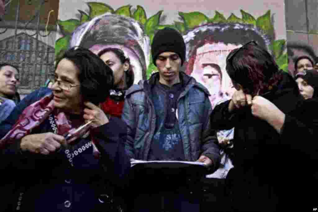 지난달 25일 이집트 카이로의 타흐리르 광장에서 새 헌법에 항의하는 의미로 머리카락을 자르며 시위하는 여성들.