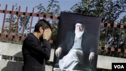 Seorang pejalan kaki memberikan doa ketika melewati poster almarhum mantan presiden Burhanuddin Rabbani yang terbunuh (foto:dok).