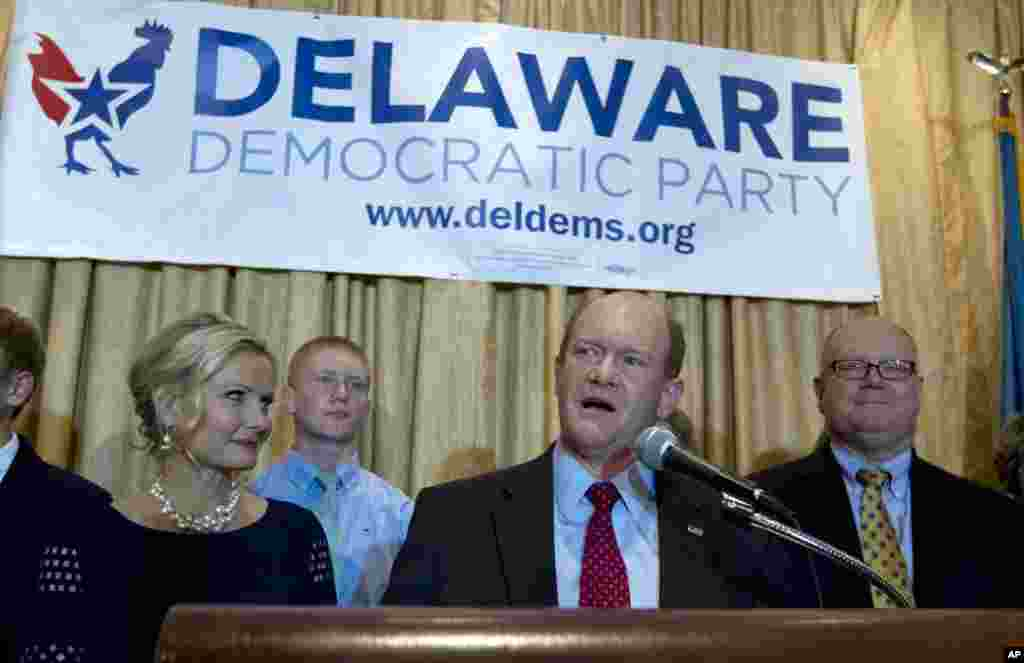 Sen. Chris Coons D-Del., accompanied by his wife Annie, left, and family, speaks to supporters after winning his re-election bid for the Senate, Tuesday, Nov. 4, 2014, during election night party in Newark, Del.