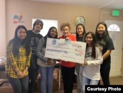 马里兰州的卡登什尔市紧急援助中心(Catonsville Emergency Assitance) 执行主任邦妮·哈利(Bonnie Harry) 接受卡登什尔高中的捐款。(CEA提供)
