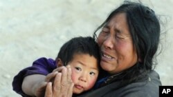 Quake survivor Sonammon, 52, who lost ten members of her family from the recent earthquake, gestures in prayer while holding onto her nephew in Jiegu, Yushu County, on April 16, 2010. The death toll from the strong earthquake in northwestern China has ris